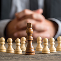 man_sitting_behind_chess_pieces_blog_square_200x200