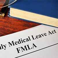 family medical leave act on paper with book glasses and pens